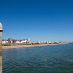 A tap stands on Brighton Pier looking back at the shoreline